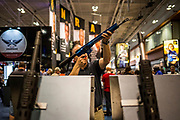 People browse the selection of guns at the NRA Annual Meeting in Nashville, Tenn. (The New York Times)