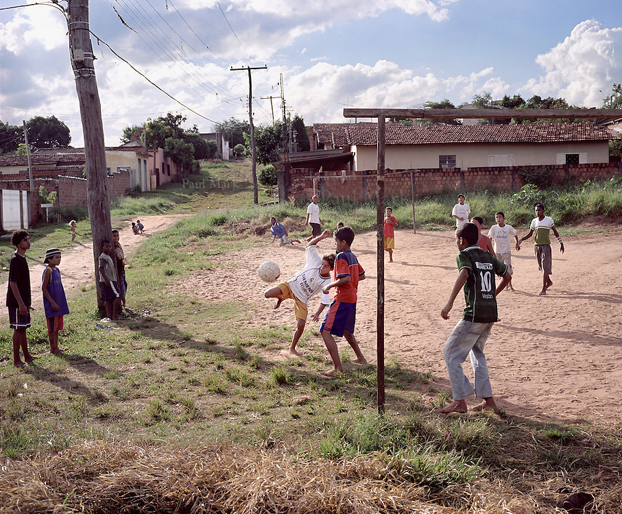 Boys play football barefoot in a favela of Bauru - the town where Pelé grew up and played as a boy.
