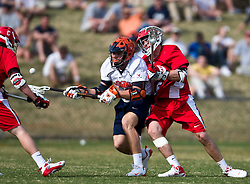 Virginia Cavaliers M/A John Haldy (12) handles a loose ball in front of Cornell Big Red LSM/D Pierce Derkac (5).  The #1 ranked Virginia Cavaliers defeated the #4 ranked Cornell Big Red 14-10 at Klockner Stadium on the Grounds of the University of Virginia in Charlottesville, VA on March 8, 2009.