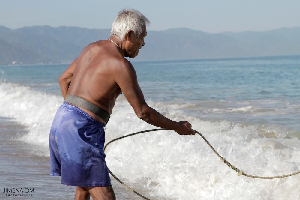 Don Esteban tira de la cuerda de una lancha frente a la Cooperativa de Pescadores Rosita, en Puerto Vallarta.