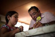 Miguel Angel Viloria (d) revisa la tarea de su hija Yuliana (i) en casa de los abuelos paternos. Gracias a FundaHigado, Yuliana recibió un trasplante de higado que le permite disfrutar de la vida. Punto Fijo, Venezuela 26 y 27 Oct. 2012. (Foto/ivan gonzalez)