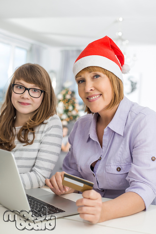 Portrait of mother and daughter shopping online during Christmas