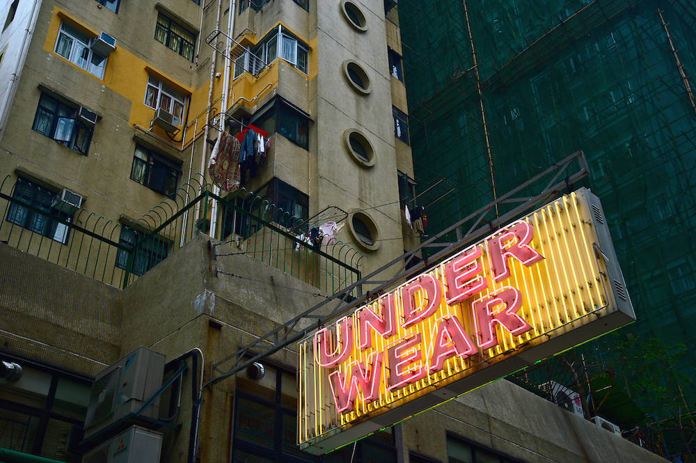 Neon sign advertising underwear beneath laundry hung out to dry, Wan Chai, Hong Kong