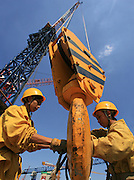 Workers attach steel rods on a crane to lift something on China World Tower 3 building's construction site in Beijing, China, Monday, August 21,  2006. Photo by Servais Mont/Pictobank