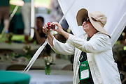 """Lynda Ream takes pictures during a performance by the Ohio Alumni Varsity Band during a barbecue on the College Green on May 31, 2014. The event, for Ohio University alumni and their families, was part of the """"On The Green"""" weekend, which was hosted by the Ohio University Alumni Association. Photo by Lauren Pond"""