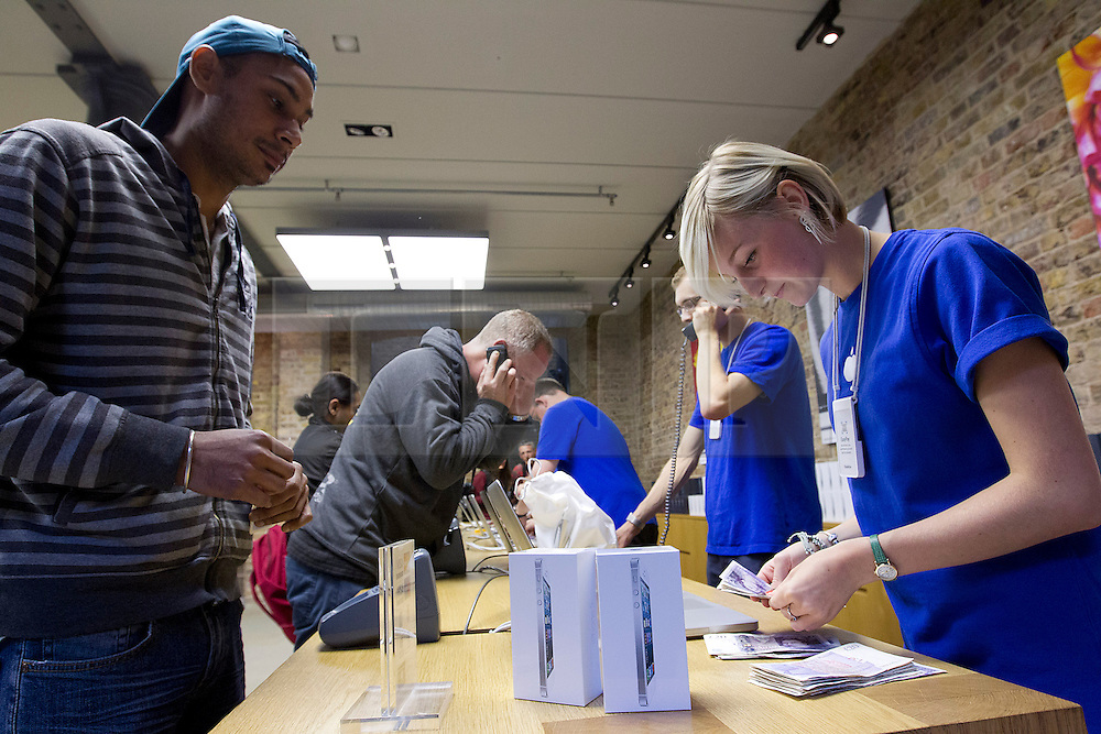 © Licensed to London News Pictures. 21/09/2012. LONDON, UK. A member of Apple store staff counts through the cash handed to her by a customer purchasing an iPhone 5 in Apple's Covent Garden store in London today (21/09/12). The iPhone 5, Apples latest mobile phone, went on sale in the UK today, with customers restricted to just two phones per-person and many buying in cash. Photo credit: Matt Cetti-Roberts/LNP