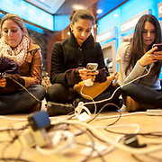 October 31, 2012 - New York, NY : From left, Robyn Taragan, Shalini Vora, and Robbie Tran, who are roommates in an apartment building on 33rd Street which is without power, use (and recharge) their cell phones in the lobby of a Chase Bank at East 41st Street and 3rd Avenue on Wednesday evening. The location was popular with residents of lower Manhattan who made their way north in search of electricity and internet connections. CREDIT: Karsten Moran for The New York Times