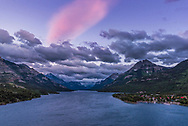 Twilight clouds over Upper Waterton Lake from the Prince of Wales Hotel viewpoint on a very windy evening! While the lower clouds are dark against the bright sky, there remains a high-altitude cloud lit by the red light of the long set Sun. The Waterton townsite and boat docks are at lower right.<br /> <br /> With the 24mm Sigma lens and Nikon D750. Taken as part of a 700-frame motion-control time-lapse.