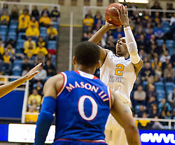 West Virginia Mountaineers guard Jevon Carter (2) shoots a three pointer against the Kansas Jayhawks during the second half at the WVU Coliseum.