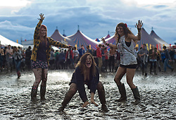 © Licensed to London News Pictures. 26/08/2011. Reading, UK. L to R Rosie Wallace (18) , Katherine Vincent (18) and Jo Bligh enjoying the mud on day one of Reading Festival 2011 in Reading, Berkshire today (26/08/2011). Photo credit: Ben Cawthra/LNP