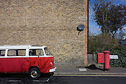 A parked red VW camper van parked next to a faded red Royal Mail postal box on a residential street in Herne Hill, London SE24.