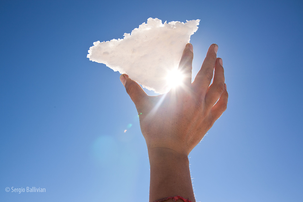 A hand holds a thin piece of salt on the Salar de Uyuni in Bolivia's Altiplano.