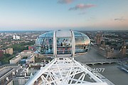 Tourists look out of the aerial view provided by the London Eye.