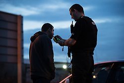 © Licensed to London News Pictures . 20 December 2013 . Manchester , UK . The Inspector breathalises a man who had been stopped near to the Trafford Centre after he was spotted using a hand held mobile phone whilst driving . Man blew a zero . A Mad Friday shift with Inspector Matt Bailey-Smith , of Greater Manchester Police's ANPR and Tactical Vehicle Intercept Unit . Photo credit : Joel Goodman/LNP