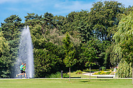 A picture of two runners captured going past a water feature in the Østerbro park in Copenhagen.
