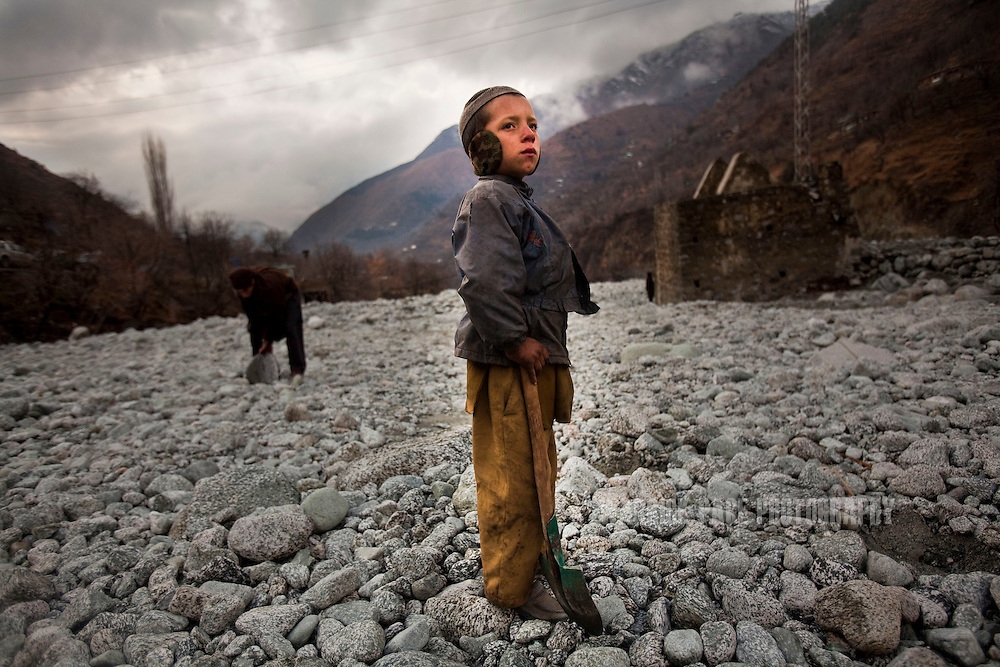 A young boy stands with a shovel as villagers collect rocks and boulders to be used for a walking path in a flood-affected village on 24 February, 2011, in Madyan, Swat Valley, Pakistan. Extreme poverty, poor diet and health, exposure to disease, and inadequate sanitation and hygiene annually produce alarming levels of malnutrition amongst children, but the floods of 2010 and 2011 have increasingly endangered an already vulnerable population. Child malnutrition has breached emergency levels in Pakistan - particularly Sindh province - after monsoon floods devastated the country's poorest region for a second year. Malnourishment It is the single biggest contributor to under-five mortality, increasing the risk of infections and slowing recovery from illness. It stuns both mental and physical growth and their future capacity, sapping the next generation's ability to meet the demands of a country already facing an unstable future. According to UN reports, hundreds of thousands of children in Pakistan suffer from severe-acute-malnutrition, with 15.1% of children experiencing acute malnourishment. The Economist recently reported that 44% of children in Pakistan suffer from varying degrees of malnutrition. (Photo by Warrick Page)