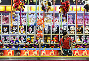 Game operator, Alex Smith, is surrounded by stuffed animals while waiting for guests to come play at the Gwinnett County Fair on Tuesday at the Gwinnett County Fairgrounds in Lawrenceville. (Staff Photo: David Welker)