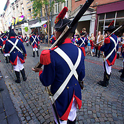Napoleonic soliders march just ahead of the Ath Giants during the Ducasse d'Ath 2011
