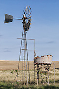 Windmill and rusted water tank in farm paddock in rural country Alectown, New South Wales, Australia.