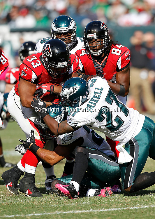 Atlanta Falcons running back Michael Turner (33) runs the ball and gets tackled by Philadelphia Eagles safety Quintin Mikell (27) and an unidentified Eagles teammate during the NFL week 6 football game against the Philadelphia Eagles on Sunday, October 17, 2010 in Philadelphia, Pennsylvania. The Eagles won the game 31-17. (©Paul Anthony Spinelli)