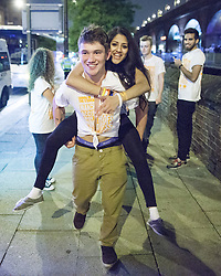 "© Licensed to London News Pictures . 22/10/2012 . Manchester , UK . A male student gives a female student a piggy back through the crowd . Students attend a Carnage UK pub crawl at bars in Manchester 's Deansgate Locks with a fancy dress theme of "" Pimps and Hoes "" . The event has been criticised for encouraging binge drinking , sexism and anti-social behaviour . Photo credit : Joel Goodman/LNP"