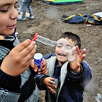 Syrian refugee kids blowing bubbles, from a tube given to him by volunteers  at collection point number 1 near Röszke. This site is a kilomtere in from a gap in the border fence along an old railway line, one of the principal access routes used by refugees entering HUngary from Serbia. Thousands of refugees crossed the border into Hungary heading towards Western Europe, until a 15 September deadline set by the Hungarian authorities to seal its border fence and bring in new restrictive laws limiting access of refugees to its territory, effectively stopping the flow of refugees.