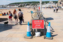 © Licensed to London News Pictures; 02/06/2020; Weston-super-Mare, UK. A sign advising social distancing is placed at an entrance to the beach. People at the beach after some lockdown restrictions due to the coronavirus covid-19 pandemic have been lifted by the UK Government. People can spend as long outdoors as they want and can meet in groups of up to six people from different households as long as they maintain social distancing of 2m or more. Photo credit: Simon Chapman/LNP.