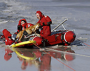 Old Lyme volunteer Jim Jewett pulls Sunny, a chow mix that fell through the ice on Rogers Lake Monday morning Jan. 21, 2002 into an inflatable boat. Sunny's owner, Kate Savage, was rescued by neighbors Betsy James and Mike Burke after she fell through the ice trying to save the dog. (Sean D. Elliot/The Day)
