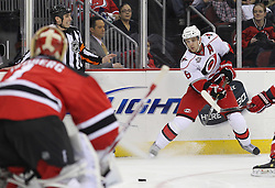 Feb 16; Newark, NJ, USA; Carolina Hurricanes center Brandon Sutter (16) takes a shot at New Jersey Devils goalie Johan Hedberg (1) during the first period at the Prudential Center.