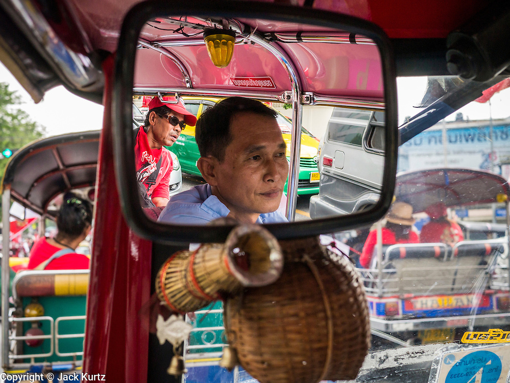 "10 DECEMBER 2012 - BANGKOK, THAILAND:  A tuk-tuk driver and his passenger in a convoy of Red Shirt ""tuk-tuks"" (three wheeled taxis) go to the Pheu Thai offices on Petchaburi Road in Bangkok Monday. The Thai government announced on Monday, which is Constitution Day in Thailand, that will speed up its campaign to write a new charter. December 10 marks passage of the first permanent constitution in 1932 and Thailand's transition from an absolute monarchy to a constitutional monarchy. Several thousand ""Red Shirts,"" supporters of ousted and exiled Prime Minister Thaksin Shinawatra, motorcaded through the city, stopping at government offices and the offices of the Pheu Thai ruling party to present demands for a new charter.        PHOTO BY JACK KURTZ"