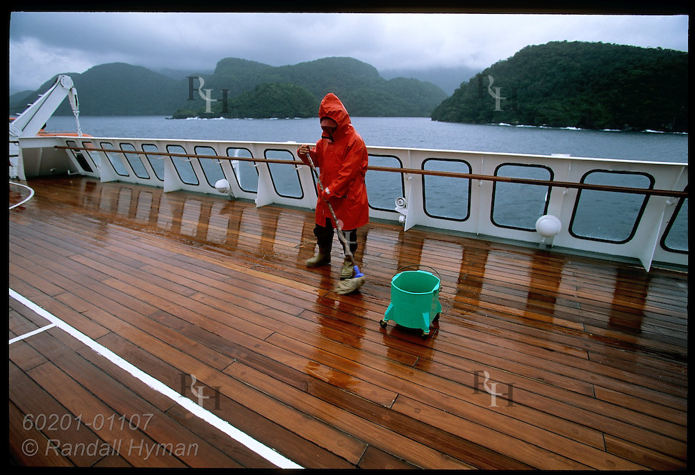 Deck hand swabs sun deck in stormy weather as Clipper Odyssey cruise ship explores Fiordland Natl Park, New Zealand.