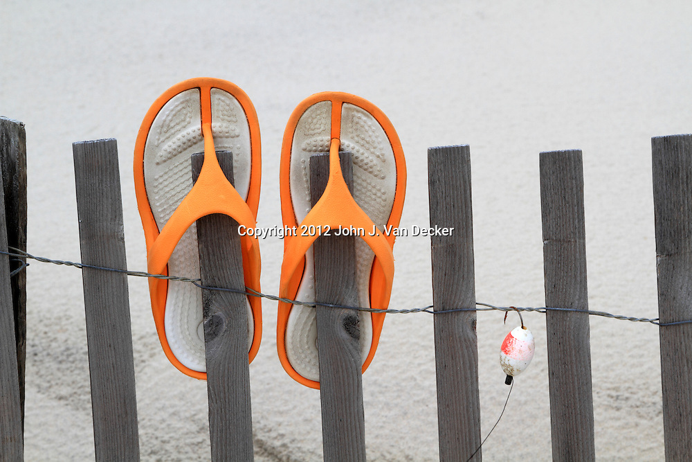 Flip Flops and fishing lure hanging on a beach dune fence. Lavalette, New Jersey, USA