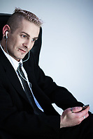 studio shot of isolated picture of a strange  businessman with piercing and tattoos listening multimedia player