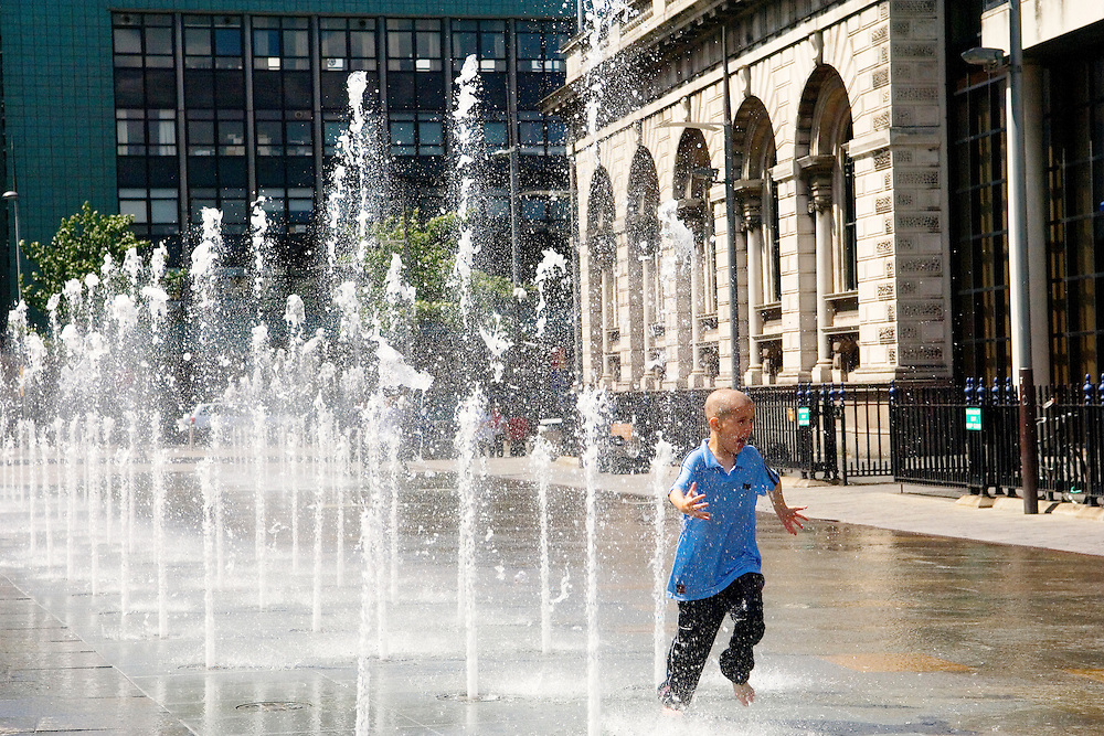Donegall Quay, Belfast, County Antrim, Northern Ireland. Boy running through Queens Square fountain beside the Custom House.