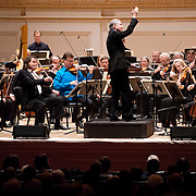 """March 27, 2012 - New York, NY : Music Director and Conductor Michael Tilson Thomas, on podium, leads the San Francisco Symphony, featuring the St. Lawrence String Quartet (seated in foreground, from left, violinists Geoff Nuttall and Scott St. John, violist Lesley Robertson, and cellist Christopher Costanza) in the New York premiere of John Adams's """"Absolute Jest"""" in Carnegie Hall's Stern Auditorium on Tuesday evening.  CREDIT : Karsten Moran for The New York Times"""