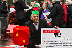 "Campaigners from Shelter Scotland raise awareness of their campaign ""Homelessness - Far From Fixed"" outside the Scottish Parliament in Edinburgh. They are joined by carol singers from Corstorphine Primary School, a Christmas tree and a giant snakes and ladders board game - Chance Not Choice - which illustrates how life chances affect people's ability to keep a roof over their head.<br /> <br /> Pictured:"