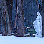 This image was shot in the first (blue) light of day.  I was struck by the warmth of the statue, the open welcoming arms, contrasted to the cold of the snow.  It almost appears that her right hand is pointing to the bench, inviting you to come and visit with her.  You can see a couple of trees in the background forming a crude cross in the background.