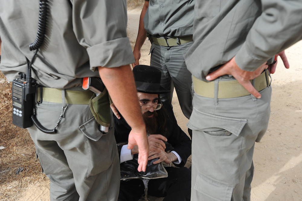 Ultra Orthodox Jewish men confronted Israeli Border Police during protests in the site of the graves relocation operation in  Barzilay hospital in the southern city of Ashkelon, May 16, 2010. Israeli government has ordered to relocate the ancient graves to a new place on Sunday may 16, so the hospital can begin to build a new protected Emergency room. Dozens of Ultra-Orthodox Jews demonstrated against the transfer of the ancient graves in order to prevent it. Photo by GILI YAARI