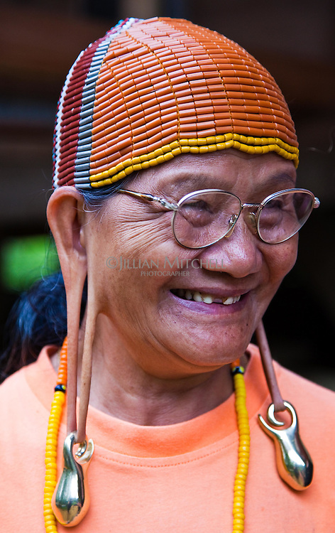 This Kelabit woman wearing traditional headware has retained her tradtional long ears, she also sports the tattoos on her legs that were a sign of beauty in her younger days.