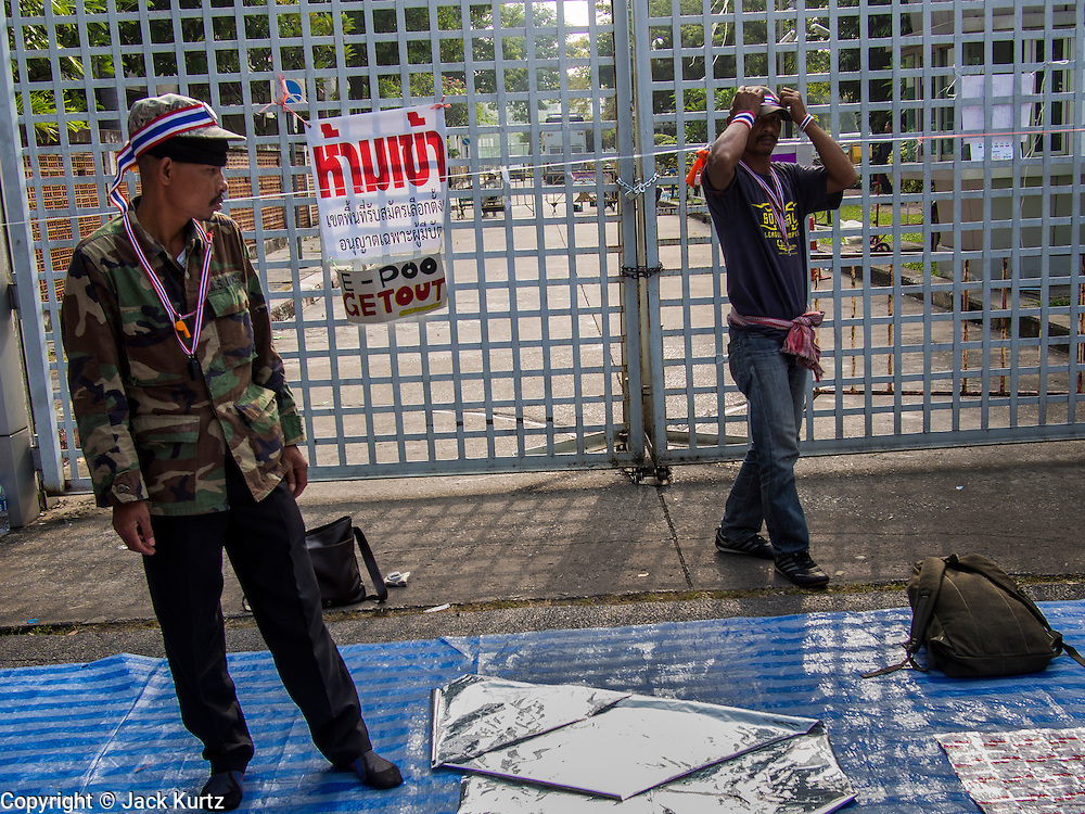 """24 DECEMBER 2013 - BANGKOK, THAILAND:  Protestors walk past one of the chained gates to the Thai-Japan Stadium in Bangkok. The sign on the gate says """"E-Poo get out,"""" E-Poo is a nickname for caretaker Prime Minister Yingluck Shinawatra. Hundreds of anti-government protestors are camped out around the Thai-Japan Stadium in Bangkok, where political parties are supposed to register for the election on February 2. As of Dec 24, nine of the more than 30 parties were able to register. Protestors hope to prevent the election. The action is a part of the ongoing protests in Bangkok that have caused the dissolution of the elected government.     PHOTO BY JACK KURTZ"""