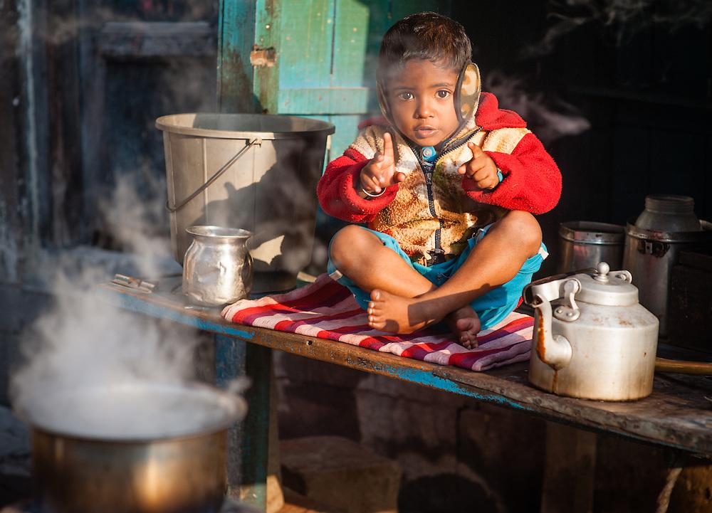 Boy with ear protectors at tea stall in Varanasi (India)