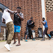 Péto (second from the left) is a national fom DRC who arrived in South Africa when he was 18. He was granted asylum status. Because of the lack of job opportunities in the country, he is now training everyday at the Yeoville Community Center to qualify as a professional heavyweight boxer to make a living. 03 March 2017. Johannesburg, South Africa. © Miora Rajaonary/ Native Agency