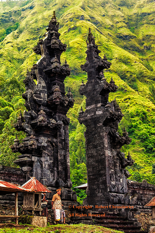 Temple-Pura Bale Agung: The imposing Pura Bale Agung entrance way, a Balinese Hindu Temple set at the base the Batur volcanic crater in tropical Trunyan Bali Indonesia.<br /> <br /> Men stand awaiting worshipers to attend a ceremony to repair the temple and to mourn the dead.