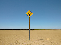 Double arrow sign on arid landscape