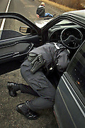 The debate over profiling reaches small towns, as Washington State Patrol Trooper Matt Couchman searches a car he stopped in Yakima, Washington. The passenger sits handcuffed after he was found in posession of  methamphetamine. <br /> (published 1/5/03)