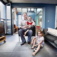 Nederland, Amsterdam , 7 juli 2010..Eberhard van der Laan thuis in zijn woning op de Baron G.A. Tindalplein 207, trekt de schoenen van zijn kinderen aan alvorens ze naar de creche worden gebracht..Vanmiddag, woensdag 7 juli, wordt de nieuwe burgemeester van Amsterdam geïnstalleerd. Eberhard van der Laan (55) zit de komende zes jaar op 'de mooiste stoel van de stad'..On the day of his inauguration as mayor of Amsterdam,Eberhard van der Laan dresses his children before they are brought to the creche.