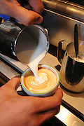 preparing cappuccino Adding hot milk froth to coffee