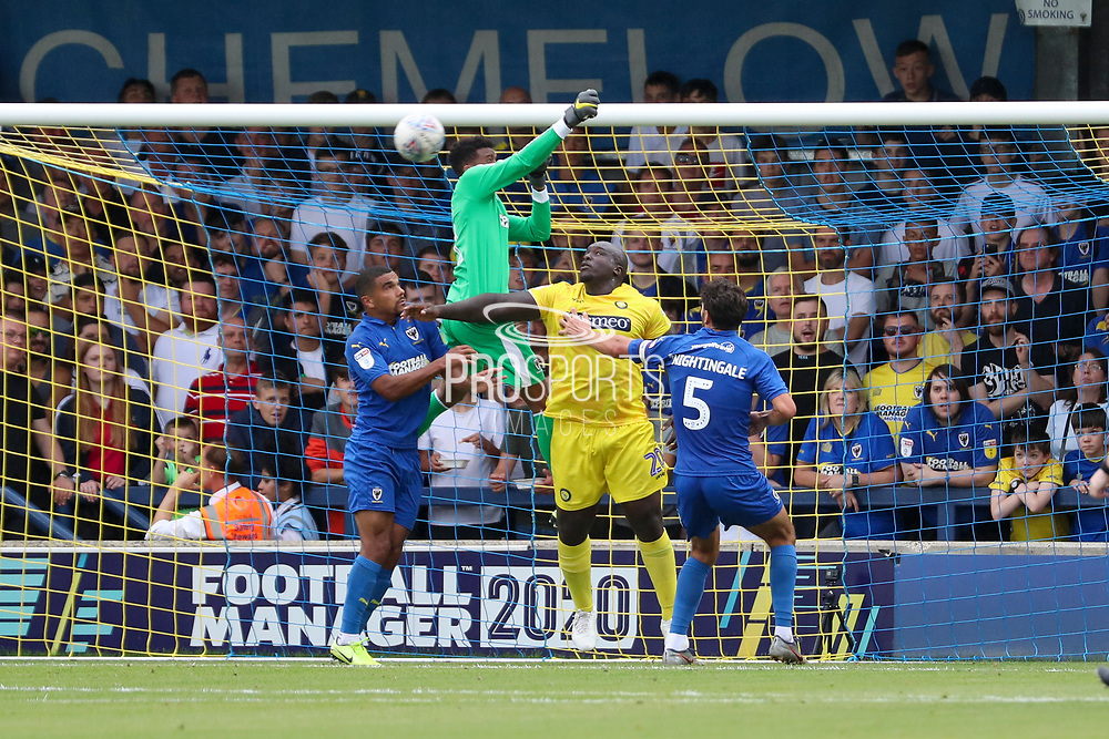 AFC Wimbledon goalkeeper Nathan Trott (1) battles for possession with Wycombe Wanderers attacker Adebayo Akinfenwa (20) during the EFL Sky Bet League 1 match between AFC Wimbledon and Wycombe Wanderers at the Cherry Red Records Stadium, Kingston, England on 31 August 2019.