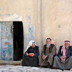 Three old men sitting down on the floor in the old village of Dana, Jordan, Asia.