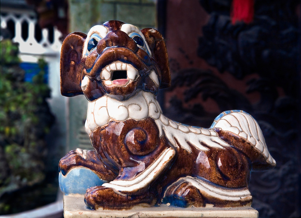 Life size ceramic figure of a guardian dog, stylized Pekingese type, at the entrance of a pagoda in North Vietnam. It snarls, showing teeth.